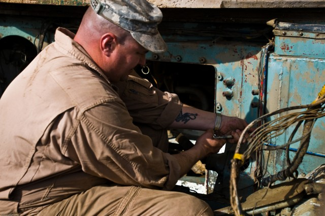 Sergeant Mark Wheeler, Company B, 26th Brigade Support Battalion, 2nd HBCT, examines wiring inside the tank engine compartment to determine its serviceability.  He plans to have the engine operational in a month and fully mission capable in three months.