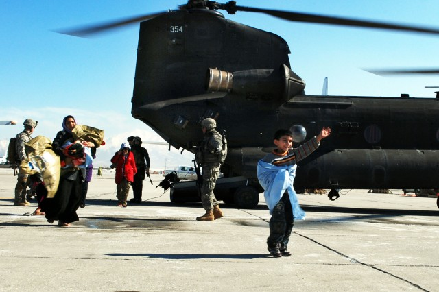 An Afghan boy waves after he and other Afghans walk out of a Chinook with B Co., Task Force Knighthawk, 3rd Combat Aviation Brigade, TF Falcon, Feb. 9 at Bagram Airfield, Afghanistan. The boy and other Afghans were victims of an avalanche that occurred the evening before, north of Bagram.
