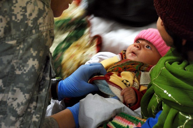 Pvt. 1st Class Nichole Hill, medic with Task Force Workhorse, 3rd Combat Aviation Brigade, TF Falcon, checks the vitals on a Afghan baby, Feb. 9, at Bagram Airfield, Afghanistan. The baby was a victim of an avalanche that occurred the previous evening north of Bagram.