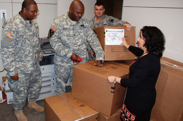 From left, Sgt. James Reece, Sgt. 1st Mark Jackson and Sgt. Ralph Brown, all of the 470th Military Intelligence Brigade, and Camilla Weeks, brigade Family Readiness Support Assistant, complete packing boxes of clothing destined for Haiti.