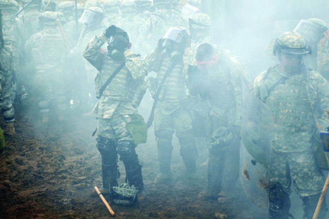 """Soldiers of the 1-144th Maneuver Task Force, Multi-National Battle Group -East in Kosovo, don their protective masks amid a layer of  gas on Camp Bondsteel, Kosovo, during crowd-and-riot-control maneuvers, part of a train-up for MNBG-E's recent """"Full Operational Capable Exercise.""""  The FOC tested the Battle Group's ability to respond to incidents quickly throughout Kosovo. UT was part of a validation process that all five KFOR Battle Groups underwent."""