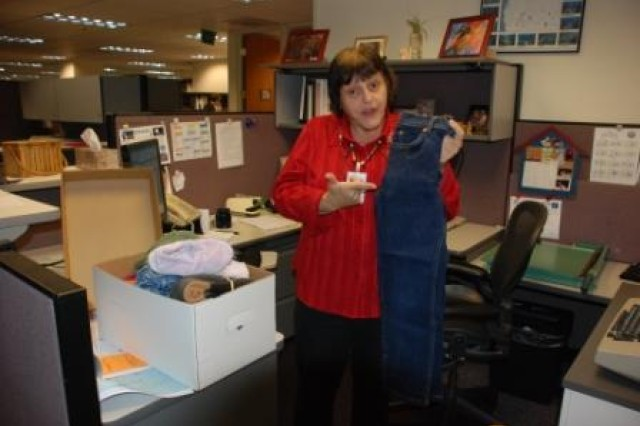 Shirley Glover, Programs and Project Management Division, holds up a pair of jeans she bought for 39 cents at a local thrift store.  She plans to send them as part of a donation to the Volunteer Community Relations program.
