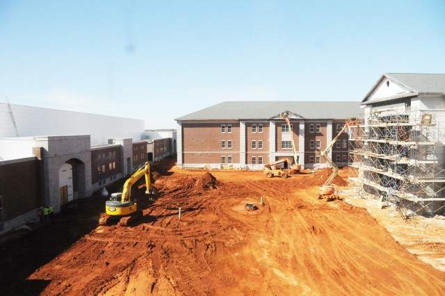 Brasfield and Gorrie construction crew members complete some exterior work on the new Enterprise High School Friday. The open area will serve as a courtyard for students when the school opens in August.