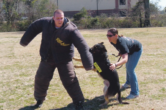 Handler SGT Amy Meyer demonstrates military working dog Bak's abilities against an attacker with volunteer Hollis Rogers' help Saturday during a canine demonstration for Troop 27.