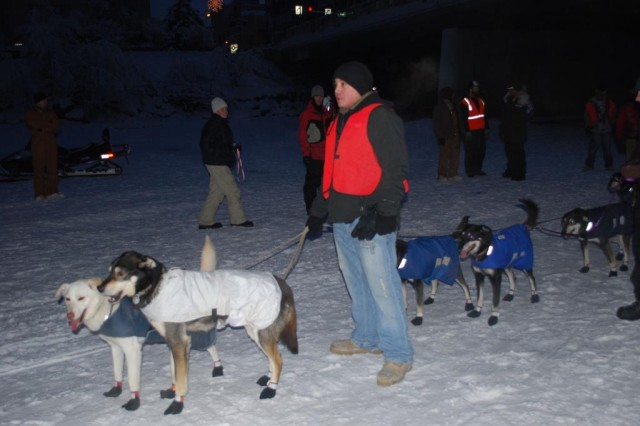 Spc. Jordales Not Afraid, 2nd Battalion, 8th Field Artillery Regiment, escorts mushers and their dogs to the start line of the 2010 Yukon Quest International Sled Dog race in Fairbanks Feb. 6.