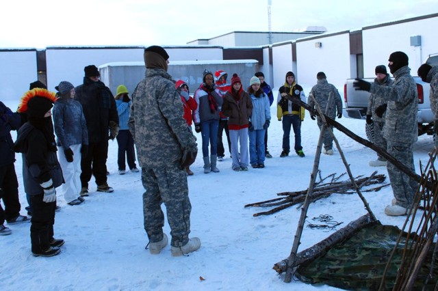 Soldiers from the 5th Squadron, 1st Cavalry Regiment, 1st Stryker Brigade Combat Team, 25th Infantry Division, demonstrate improvised shelters during cold weather survival classes Feb. 5 at Tanana Middle School in Fairbanks, Alaska.