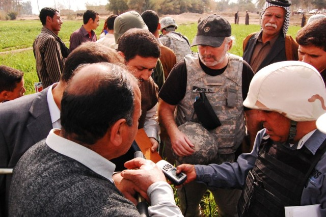 Dr. Mohamed, a Diwaniayah Provincial Reconstruction Team leader, teaches members of the Director General and local farmers how to plot points using a global positioning system Feb. 16, 2010, at a farm in Diwaniyah, Iraq. Bill Baker, another PRT leader, observes the training.
