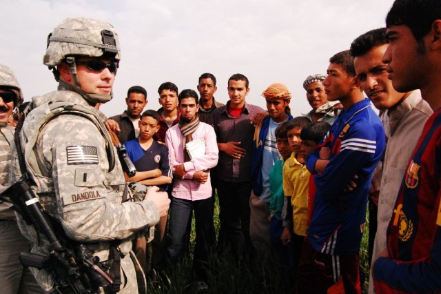"""First Lt. Matthew Dandola, a civil affairs team leader attached to the 1st Battalion, 15th Infantry Regiment, 3rd Heavy Brigade Combat Team, 3rd Infantry Division, talks to local children Feb. 16, 2010, as leaders of the 1st Bn., 15 Inf. Regt., the Diwaniyah Provincial Reconstruction Team and members of the Director General take soil samples in Diwaniyah, Iraq. The samples were taken to determine if land was suitable for """"tunnel houses,"""" low-tech versions of greenhouses."""