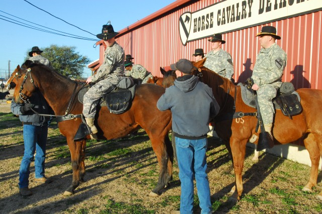 A group of Soldiers from 2nd Special Troops Battalion, 2nd Brigade Combat Team, 1st Cavalry Division, line up with horses from the Horse Cavalry Detachment, 1st Cav. Div. during a photo shoot on Fort Hood, Texas, Feb. 17. Although the STB is one of the newest units to join the cavalry, it is already working hard to fit in with the longstanding cavalry traditions.