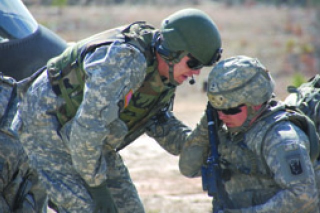 Staff Sgt. Nathan Brown (left) gives guidance to a Soldier during a live-fire exercise Feb. 19 at Fort Polk's Peason Ridge training area. Brown lost the lower portion of his right leg when his vehicle ran over a land mine in Iraq.