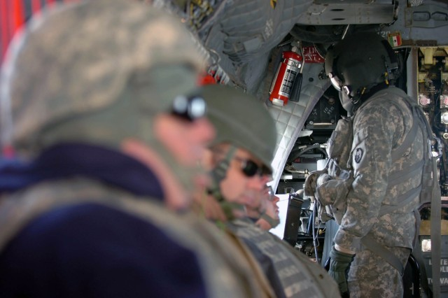 "Sgt. Ruben Torres, door gunner, Company B ""Hillclimbers,"" 3-25th General Support Aviation Battalion, Task Force Hammerhead, scans for obstacles at take-off during a troop and cargo movement mission from Contingency Operating Base Speicher, near Tikrit, Iraq, Jan. 29. Since operations began in September 2009, the Hillclimbers have flown more than 3,200 hours, transported in excess of a million pounds of cargo and moved about 10,000 military and civilian personnel.   (Photo by: Staff Sgt. Mike Alberts  25th Combat Aviation Brigade Public Affairs)"
