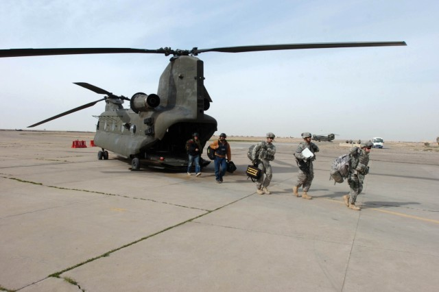 "Military and civilian passengers disembark a Company B ""Hillclimbers,"" 3-25th General Support Aviation Battalion, Task Force Hammerhead, CH-47D Chinook helicopter at Contingency Operating Base Speicher, near Tikrit, Iraq, Jan. 29. A CH-47D Chinook helicopter can transport 30 passengers and internally load up to 15,000 pounds of cargo.  (Photo by: Staff Sgt. Mike Alberts  25th Combat Aviation Brigade Public Affairs)"