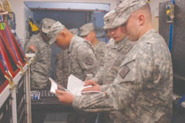 Spc. Joshua Harvey, 51st Chemical Company, 83rd Chemical Battalion (center right) shows leaders from 48th Chemical Brigade around a standard automotive tool set in the 83rd Chem motorpool Feb. 17. 1st Sgt. Courtney Murray, A Company, 22nd Chemical Battalion (left) and Command Sgt. Maj. Raymund Dimatulac, 22nd Chem (left center), examine a drawer of tools, while 1st Sgt. Donald Martin, 21st Chemical Company, 83rd Chem Bn (right), learns about the SATS inventory. The 22nd Chem Bn is based in Aberdeen Proving Grounds, Md. and the 21st Chem Co is located at Fort Bragg, N.C.