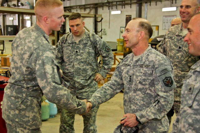 CAMP TAJI, Iraq – Lt. Gen. Charles Jacoby (right), from Fort Lewis, Wash., deputy commanding general of operations for U.S. Forces–Iraq, presents a coin for hard work and dedication to Spc. Nicholas Duncan, from Bothell, Wash., an AH-64D Apache attack helicopter maintainer in Company B, 615th Aviation Support Battalion, 1st Air Cavalry Brigade, 1st Cavalry Division, U.S. Division–Center, Feb. 24.
