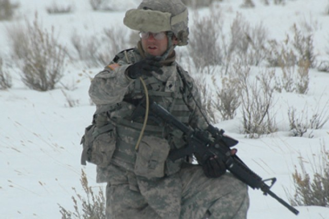 Spc. Mathew Armstrong, artillerymen, Battery B, 5th Battalion, 25th Field Artillery Regiment, 4th Brigade Combat Team, 10th Mountain Division, signals for forward movement during squad movement exercises on Camp Williams, Utah, Feb. 15.