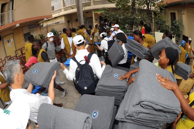 """100226-N-6214F-104 PORT-AU-PRINCE, HAITI - (February 26, 2010) Members from the Bouddhiste Tzu Chi Foundation hand out 2,000 blankets and tarps to Haitian citizens. The United States and other international military and civilian aid agencies are conducting humanitarian and disaster relief operations as part of Operation Unified Response in the aftermath of the earthquake that hit the area on Jan. 12, 2010. (U.S. Navy photo by Chief Mass Communications Specialist Robert J. Fluegel/Released)"""""""