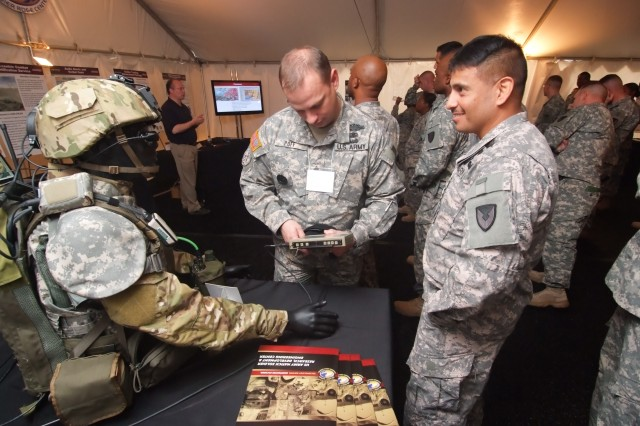 Sgt. Maj. John Poff, RDECOM Natick Soldier Systems Center and Sgt. Maj. Matthew DeLay, RDECOM operations NCO, examine Soldier System technologies that were assessed at E09. As an Army capital investment, the PM is a research and development program of record that supports Army, DoD and industry technology development efforts by providing a relevant environment to assess emerging technologies in a C4ISR system-of-systems.