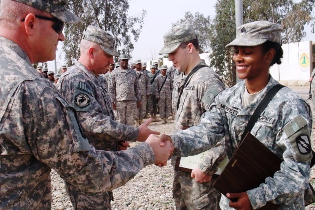 CONTINGENCY OPERATING LOCATION Q-WEST, Iraq - 1st Sgt. Troy D. Scott (left foreground), of Pearl, Miss., awards a command sergeant major's award to Sgt. Victoria M. Moffett (right foreground), of Collins, Miss., while Command Sgt. Maj. Perry Campbell (middle left), of Senatobia, Miss., bestows a brigade commander coin on Sgt. Kyle R. Stegall, of Sugarland, Texas during a ceremony here Feb. 15. Moffett and Stegall were each recognized for embodying one of the seven Army values, selfless service and respect, respectively. These Mississippi Guard members are gun truck commanders with convoy security units, Moffett serving with A Company, 106th Brigade Support Battalion, out of Magee, Miss., and Stegall serving with C Company, 2nd Battalion, 198th Combined Arms, an armor company out of Oxford and Indianola, Miss., both units part of the 155th Brigade Combat Team, headquartered in Tupelo, Miss. To honor outstanding service at the end of the deployment, the senior noncommissioned officers of the 2-198th CAB - to which A Company, 106th BSB, is attached - recognized seven Soldiers throughout the battalion, each of whom embodies one of the Army values of loyalty, duty, respect, service, honor, integrity and personal courage, said Campbell.