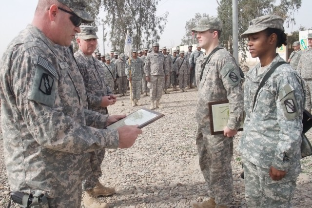 CONTINGENCY OPERATING LOCATION Q-WEST, Iraq - 1st Sgt. Troy D. Scott (left foreground), of Pearl, Miss., reads a command sergeant major's award before presenting it to Sgt. Victoria M. Moffett (right foreground), of Collins, Miss., during a ceremony here Feb. 15. Moffett and Sgt. Kyle R. Stegall (middle right, holding award), of Sugarland, Texas, were recognized for embodying one of the seven Army values, selfless service and respect, respectively. These Mississippi Guard members are gun truck commanders with convoy security units, Moffett serving with A Company, 106th Brigade Support Battalion, out of Magee, Miss., and Stegall serving with C Company, 2nd Battalion, 198th Combined Arms, an armor company out of Oxford and Indianola, Miss., both units part of the 155th Brigade Combat Team, headquartered in Tupelo, Miss. To honor outstanding service at the end of the deployment, the senior noncommissioned officers of the 2-198th CAB - to which A Company, 106th BSB, is attached - recognized seven Soldiers throughout the battalion, each of whom embodies one of the Army values of loyalty, duty, respect, service, honor, integrity and personal courage, said Command Sgt. Maj. Perry Campbell (pictured second from left), of Senatobia, Miss.