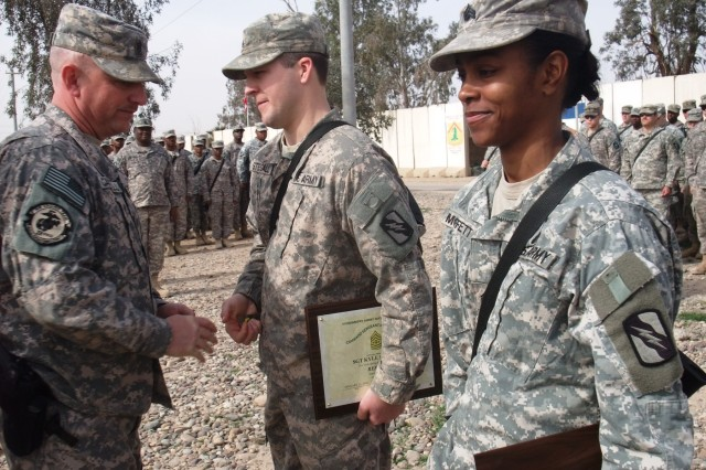 CONTINGENCY OPERATING LOCATION Q-WEST, Iraq - Command Sgt. Major Perry Campbell (left), of Senatobia, Miss., bestows brigade commander deployment coins to Sgt. Kyle R. Stegall, of Sugarland, Texas, and Sgt. Victoria M. Moffett, of Collins, Miss., during a ceremony here Feb. 15. The ceremony was to present command sergeant major's awards to Stegall and Moffett for embodying the Army values of respect and selfless service, respectively. Stegall serves as a scout gun truck commander with C Company, 2nd Battalion, 198th Combined Arms, 155th Brigade Combat Team, an armor company out of Oxford and Indianola, Miss., and Moffett is a gun truck commander with A Company, 106th Brigade Support Battalion, 155th Brigade Combat Team, out of Magee, Miss. To honor outstanding service at the end of the deployment, the senior noncommissioned officers of the 2-198th CAB - to which A Company, 106th BSB, is attached - recognized seven Soldiers from throughout the battalion who embody one of the Army values of loyalty, duty, respect, service, honor, integrity and personal courage, said Campbell.