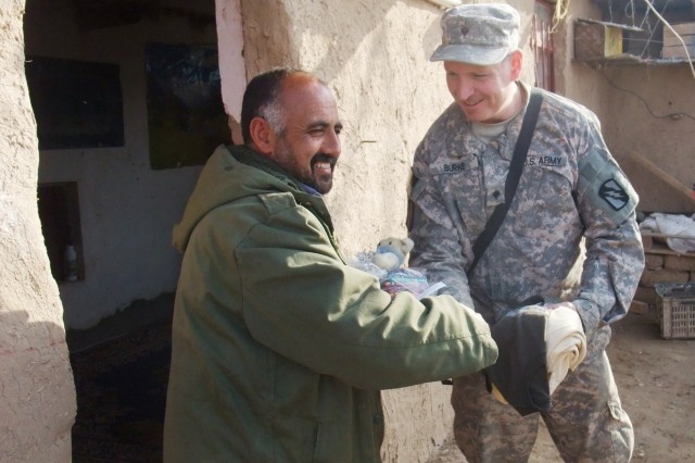 CONTINGENCY OPERATING LOCATION Q-WEST, Iraq -Khalil Abrahim (left), a farmer who grows wheat and raises sheep near Al Qayarrah, shakes hands with Spc. Daniel Burke, a gun truck driver from Apalachicola, Fla., when Burke and other members of his unit brought gifts of clothing and toys to the farmer during a security escort mission to the Tigris River pump house that supplies water to Q-West, Feb. 5. Burke serves with A Company, 2nd Battalion, 198th Combined Arms, 155th Brigade Combat Team, out of Hernando, Miss., the Q-West force protection company that provides security to all missions to the pump house or along the water pipeline, among the unit's numerous other missions. The Soldiers of A Company solicited from home gifts of clothing, linen, toys, school supplies and other items to give Abrahim and his family, whom they befriended during their many visits to the pump house.
