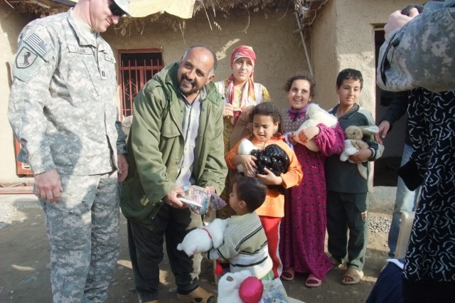 CONTINGENCY OPERATING LOCATION Q-WEST, Iraq -Capt. Drew Clark (left), a resident of Madison, Miss., looks on as Khalil Abrahim hands his son Muhammed a plastic bag of pencils and crayons, at his farm near Al Qayarrah, during a security escort mission to the Tigris River pump house that supplies water to Q-West, Feb. 5. Clark commands A Company, 2nd Battalion, 198th Combined Arms, 155th Brigade Combat Team, out of Hernando, Miss., the Q-West force protection company that provides security to all missions to the pump house or along the water pipeline, among the unit's numerous other missions. The Soldiers of A Company solicited from home gifts of clothing, linen, toys, school supplies and other items to give Abrahim and his family, whom they befriended during their many visits to the pump house.