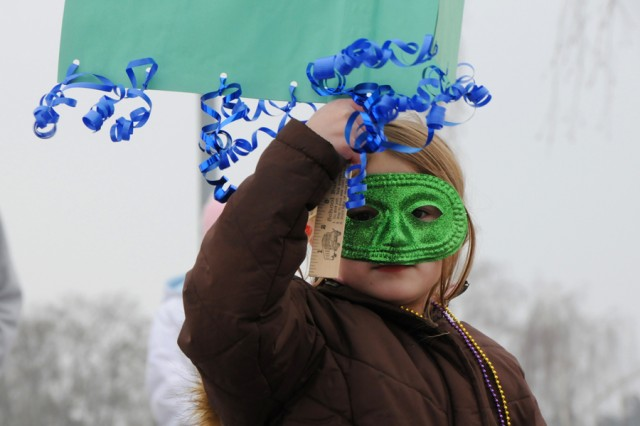 GRAFENWOEHR, Germany AcE+' Alexandria Hurkman, first-grade student at Grafenwoehr Elementary, dons a traditional Fasching mask and carries her class sign during the annual school parade.