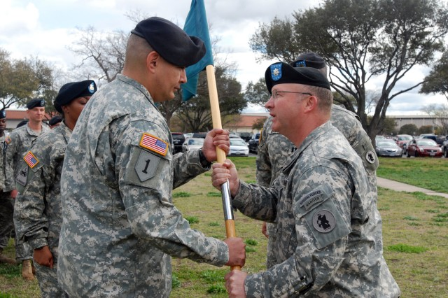 """Lt. Col. Scot Storey (right), passes the unit colors to Capt. Juan Talamantes, Jr. during a change-of-command ceremony in front of the U.S. Army South headquarters building in """"Old BAMC"""" March 1.  Talamantes received the unit colors of the Headquarters and Service Company, Special Troops Battalion, U.S. Army South from Capt. William J. Brickner, Jr. during the ceremony.  Storey is Army South's STB commander.  (Photo by Robert R. Ramon, U.S. Army South Public Affairs Office)"""