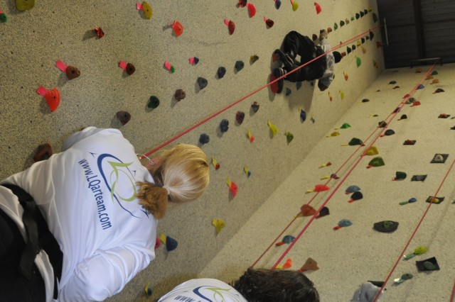 FORT CARSON, Colo.-A wounded warrior gets close to the top of the rock wall as LifeQuest volunteers help by spotting him.