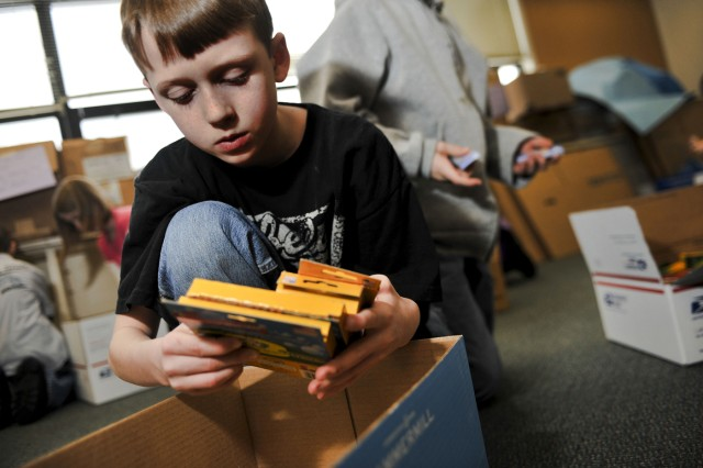 Michael Diller, a fourth grade Aurora Elementary School student at Elmendorf Air Force Base, Alaska, grabs several boxes of markers to pack one of the boxes to send to students in Konar River Valley, Afghanistan Feb. 25. During the past several weeks, students from AES's Student Council and Service Learning Club held a school supply drive, collecting pens, pencils, spiral notebooks, colored pencils, notebook paper, markers and hand-operated pencil sharpeners that will be distributed throughout 13 schools in the Konar River Valley.