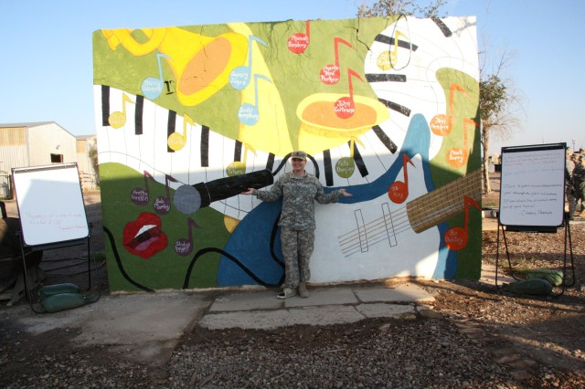 Spc. Nicole Day, a Carrollton, Ohio, native with the 1483rd Transportation Company, 541st Combat Sustainment Support Battalion, 15th Sustainment Brigade, 13th Sustainment Command (Expeditionary), poses with her finished mural. Day sketched and painted the mural outside the 1483rd Trans. Co. MWR to help the company celebrate Black History Month. (U.S. Army photo by Spc. Corine Margetiak, 1483rd Transportation Company)