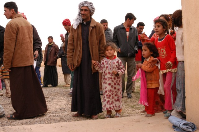 CONTINGENCY OPERATING LOCATION Q-WEST, Iraq - Townsfolk crowd into the schoolyard of Jedallah Anuk, a small village near Q-West, to receive gifts sent by the people of Barrington, R.I., and delivered by Mississippi Guardsmen, Feb. 1. Members of A Company, 2nd Battalion, 198th Combined Arms, 155th Brigade Combat Team, out of Hernando, Miss., the Q-West force protection company, delivered the packages during a routine perimeter patrol. Since 2003, Barrington has been sending clothing, school supplies and other items to Jedallah Anuk in an Adopt-a-Village program initiated by the 101st Airborne Division.