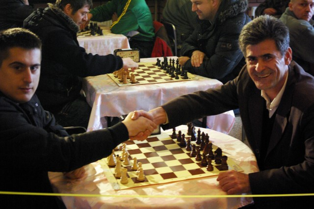 Miodrag Kropljanin, captain of the Strpce/Shterpce team, and Idriz Iseni, captain of the Donja Bitina team, shake hands before a game at a multi-ethnic chess tournament in Strpce/Shterpce Feb. 27. Players from Kosovo, Ukraine, Poland and the United States particpated in the tournament.
