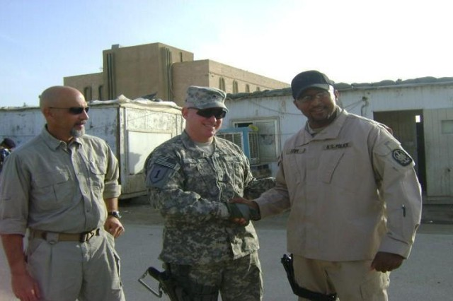 U.S. Army Brig. Gen. Ricky Gibbs, Deputy Commanding General, 1st Infantry Division greets CPATT members Chukwuemeka Atum at the Dhi Qar PJCC as John Cottle looks on.  Atum and Cottle are civilian police advisors attached to the 4th Brigade, 1st Armored Division attached to United States Division-South, Iraq.