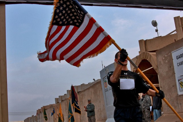 Air Force Senior Airman Matthew Klundt, from Fresno, Calif., of the 732nd Expeditionary Security Forces Squad, carries an American flag as he crosses the finish line to claim first place in the Fallen Soldier Half-Marathon run Feb. 28, in Taji, Iraq.