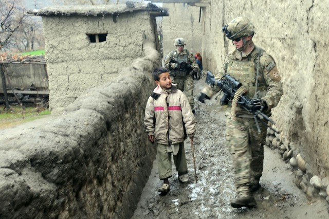 Pfc. John D. Macintosh of Chesapeake, Va., a gunner with 3rd Platoon, Chosen Company, 12th Infantry Regiment, 4th Brigade Combat Team, talks with a young resident of the Wata Poor District in the Kunar province of Afghanistan, while on patrol.