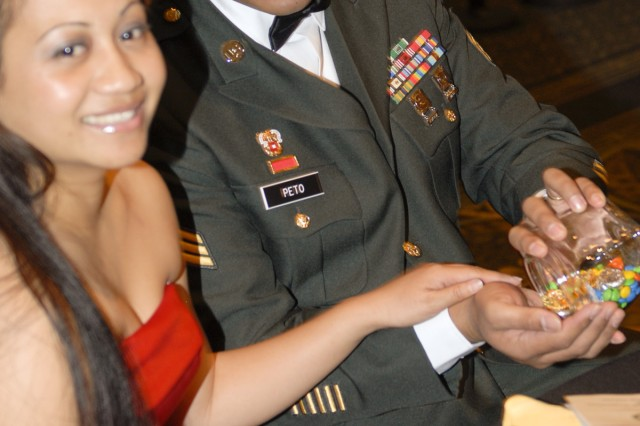 Sgt. Freddie Peto, who works in the communications section of the 3rd Brigade Special Troops Battalion, 3rd Heavy Brigade Combat Team,1st Cavalry Division enjoys an evening meal with his wife Marie during a military ball held Feb. 5 at the Killeen Civic Center. Peto, a Honolulu native, posted the nation's colors as part of the color guard for the ball.