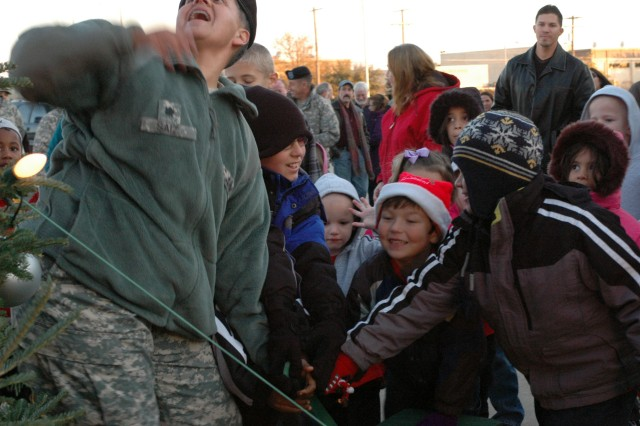 """Lt. Col. Saiz, rear detachment commander, 15th Sustainment Brigade, 13th Sustainment Command (Expeditionary) and junior """"Wagonmasters"""" light the way for Santa's arrival to the """"Wagonmasters"""" Tree Lighting Ceremony that took place, here Dec. 5.(U.S. Army photo by Cpl. Jessica Hampton, 15th Sustainment Brigade Public Affairs)"""