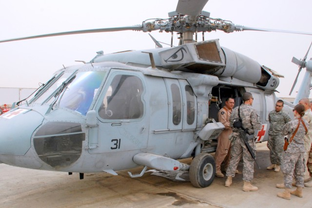 "Chief Petty Officer Curtis Trull Jr. (left), a hospitalman with the 2515th Navy Air Ambulance Detachment, gives a tour of the detachment's helicopter to instructors and students of a MEDEVAC class for members of the Iraqi Army's 14th Division, Feb. 24, 2010, at the Contingency Operating Base Basra flight line. Second Lt. Muhamad Hussam, a medical officer with the Iraqi Army's 52nd Brigade, 14th Div., who was severely wounded as a medic during the 2008 ""Charge of the Knights,"" battle for Basra, was instrumental in getting the program started, said Capt. Susan M. Mosier, the 17th FiB's surgeon."