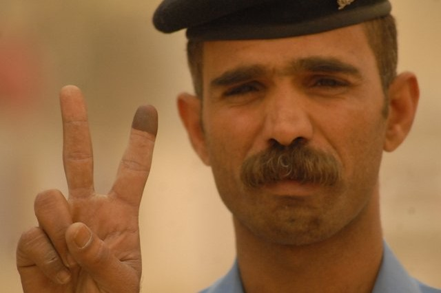 An Iraqi policeman proudly displays his ink-stained finger on the streets of Najaf Province, March 4, indicating he has voted in the special-needs election process. The early voting allowed security personnel and others to vote prior to the regular parliamentary elections scheduled for March 7.