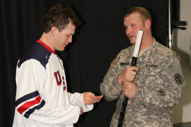 IMG_5149: Ryan Suter, defenseman for the Predators, examines the Saint Christopher's Medallion he received from Sgt. John Wawruck, squad leader for Fort Campbell's Warrior Transition Battalion. Wawruck 'adopted' Suter as part of an Operation Homefront initiative to pair Team USA Olympic hockey players with service members to help encourage the players in the 2010 Winter Olympics.