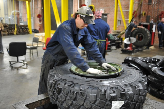 Landon Weldon puts the rim on a new tire for a Stryker at Anniston Army Depot.