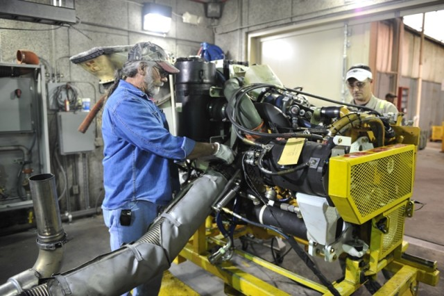 Randy Coppock (left), an Anniston Army Depot mechanic, and Stan Clopton, a General Dynamics Land Systems mechanic, prepare a Stryker power pack for testing in one of the turbine engine value stream's test cells.
