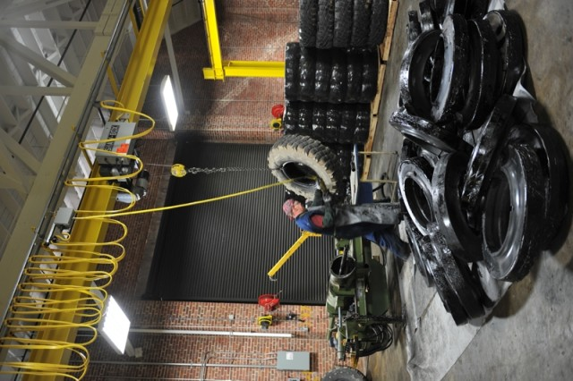 Eddie Phillips lifts a tire using an overhead crane at Anniston Army Depot. When fully assembled, each tire weighs over 400 pounds.