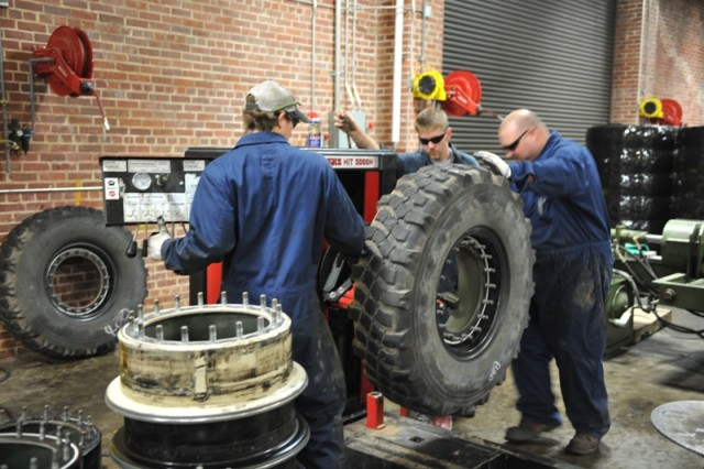 Landon Weldon (left), Rusty Phillips (rear) and Jason Parks (right) remove the rim from a Stryker tire at Anniston Army Depot.