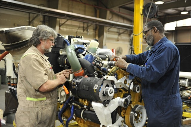 Anniston Army Depot mechanic Larry Garrett (right) and Tim Hicks, a General Dynamics Land Systems mechanic, work on a Stryker power pack.