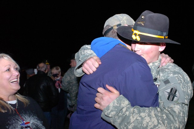 Specialist William Riley Brock (right) hugs his stepfather, Chris Watson, while the trooper's mother, Patricia, waits for hers as the 48th Infantry Brigade Combat Team of the Georgia National Guard returns from their year-long deployment to Afghanistan, March 1 at Fort Stewart.