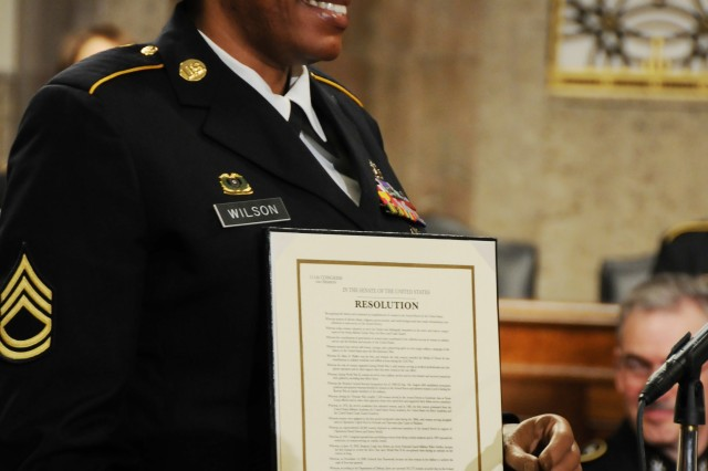 Sgt. 1st Class Juanita Wilson, a wounded warrior, accepts a Senate Resolution to recognize the accomplishments of women in the military, Thursday, during the Joint Services Women's History Month Observance on Capitol Hill.