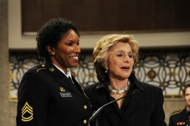 Sen. Barbara Boxer of California, right, presents a Senate Resolution to recognize the accomplishments of women in the military to Sgt. 1st Class Juanita Wilson, a wounded warrior, during the Joint Services Women's History Month Observance on Capitol Hill Thursday.