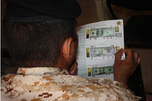 A Maysan Province policeman looks at examples of counterfeit currency during a workshop presented by U.S. Secret Service financial investigative experts at Contingency Operating Site Garryowen, near Amarah, Iraq, Feb. 20, 2010.  The course was hosted by 4th Battalion, 6th Infantry Regiment, deployed from Fort Bliss, Texas to advise and assist Iraqi Security Forces.